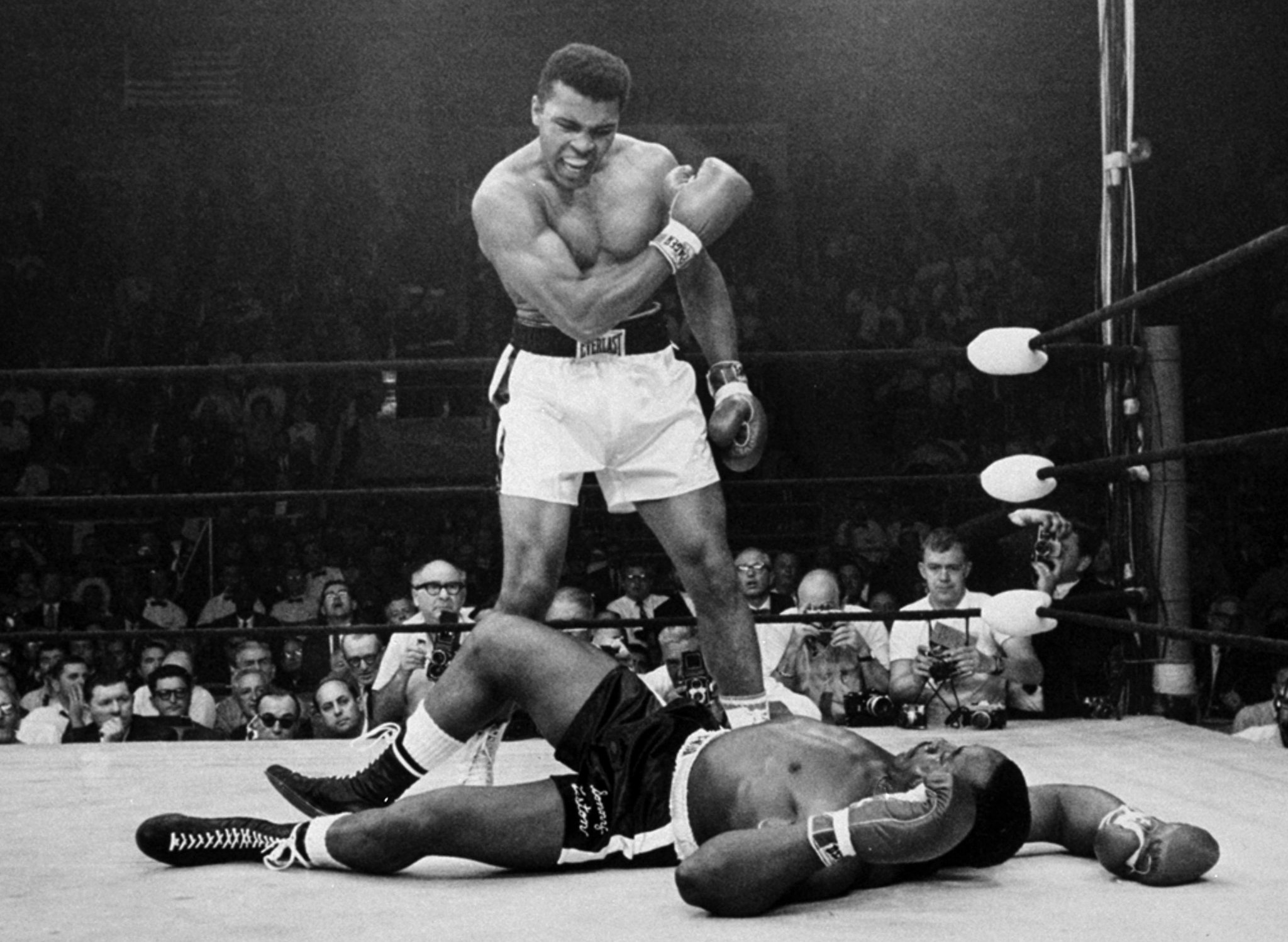 """probably the most iconic photo of his boxing career.  The short lived Ali v Liston II is still debated today.  This photo is often misinterpreted as Ali gloating but in actuality he was upset that the anchor punch had actually knocked Liston down.  """" Get up and fight sucka"""""""