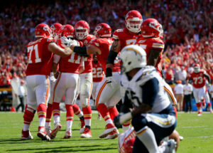 KANSAS CITY, MO - SEPTEMBER 11:  Quarterback Alex Smith #11 of the Kansas City Chiefs is congratulated by teammates after scoring a touchdown to win the game against the San Diego Chargers in overtime at Arrowhead Stadium on September 11, 2016 in Kansas City, Missouri.  (Photo by Jamie Squire/Getty Images)